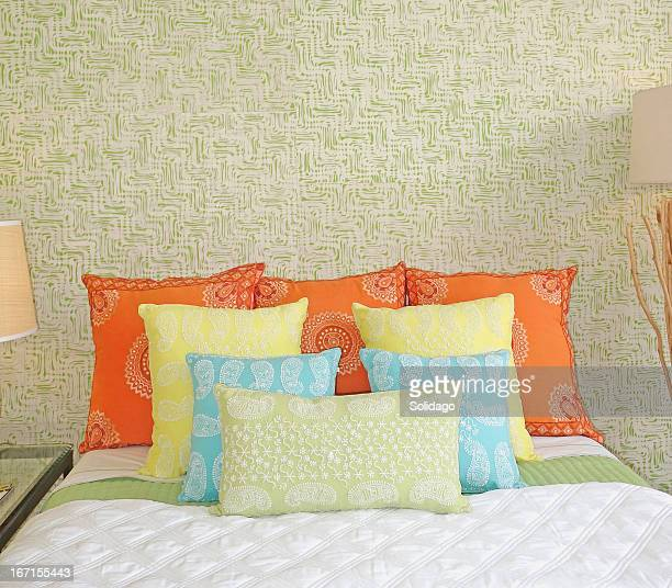 fancy embroidered cushions on bed - cushion stock photos and pictures