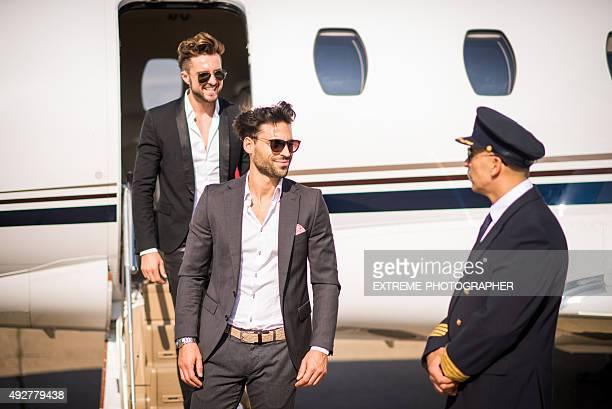 Fancy men leaving private jet airplane