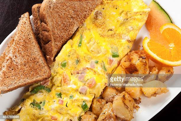 Fancy omelette including pepperstomatoesand ham served with toasts and potatoes good for breakfast or lunch