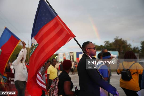 Fandzy Bernadin carries a Haitian and an American flag as he joins with others to mark the 8th anniversary of the massive earthquake in Haiti and to...