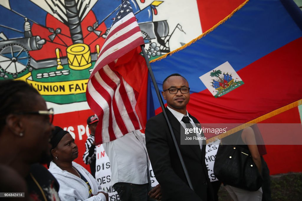 Fandzy Bernadin holds an American flag as he joins with others to mark the 8th anniversary of the massive earthquake in Haiti and to condemn President Donald Trump's reported statement about immigrants from Haiti, Africa and El Salvador on January 12, 2018 in Miami, Florida. President Trump is reported to have called those places 'shithole countries' whose inhabitants are not desirable for U.S. immigration.