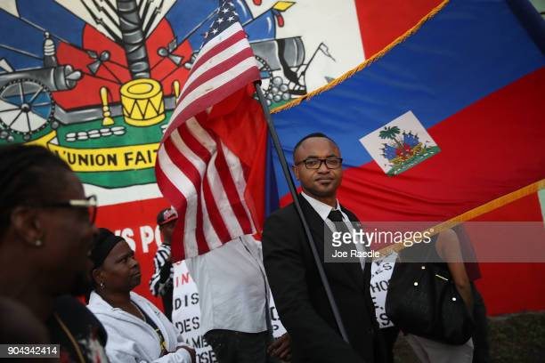 Fandzy Bernadin holds an American flag as he joins with others to mark the 8th anniversary of the massive earthquake in Haiti and to condemn...