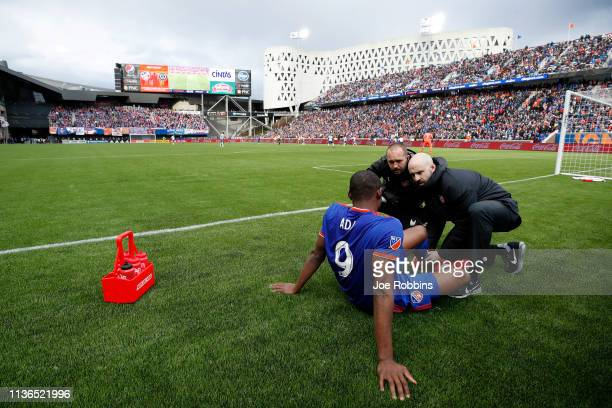Fanendo Adi of FC Cincinnati players receives medical attention on the sideline after suffering an injury against the Portland Timbers in the first...