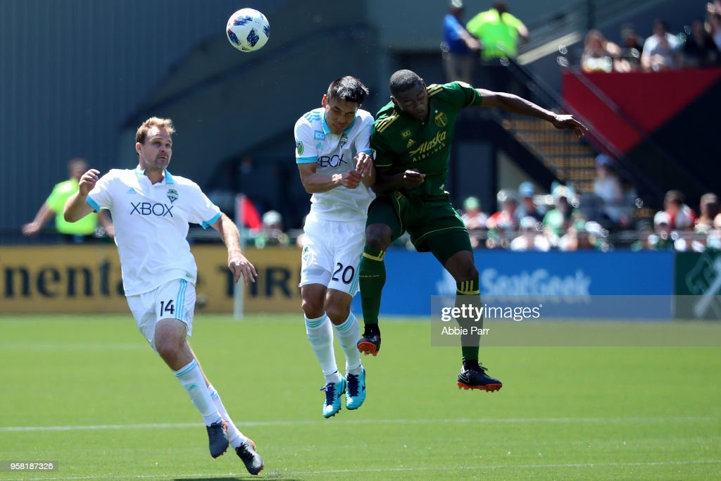 Fanendo Adi #9 of the Portland Timbers jumps for the ball against Kim Kee-Hee and Chad Marshall #14 of the Seattle Sounders in the second half during their game at Providence Park on May 13, 2018 in Portland, Oregon.