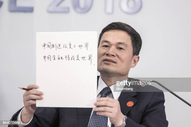 Fang Xinghai vice chairman of the China Securities Regulatory Commission holds up a notepad showing his writing during a session at the Boao Forum...