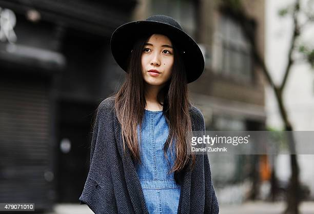 Fangyi Zou is seen around Soho wearing a Zara dress Urban Outfitters cardigan and an Urban Outfitters hat on June 30 2015 in New York City