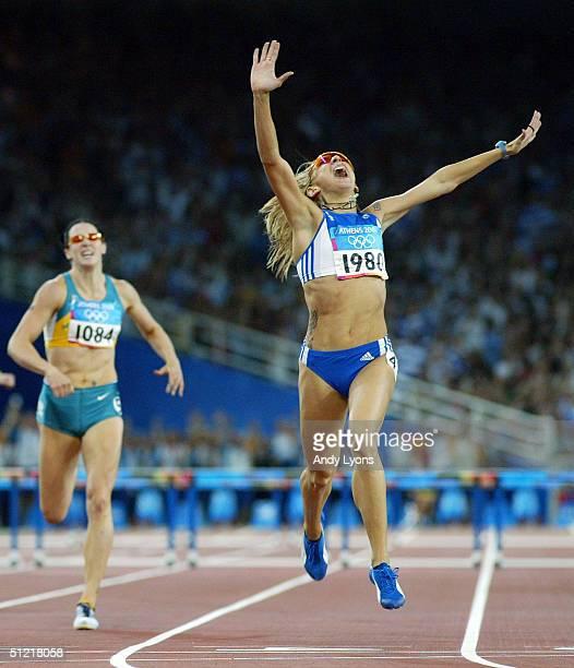Fani Halkia of Greece crosses the finish line as she celebrates infront of Jana Pittman of Australia in the women's 400 metre hurdle final on August...