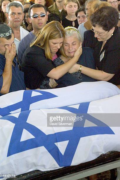 Fani Nelimov center the grandmother of bomb victims Yelena and Yulia Nelimov grieves over their flagcovered bodies June 3 2001 in a cemetery in Tel...