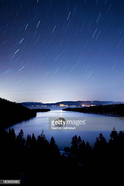 fannette island is illuminated at night with star trails over emerald bay in lake tahoe, ca. - emerald bay lake tahoe stock pictures, royalty-free photos & images