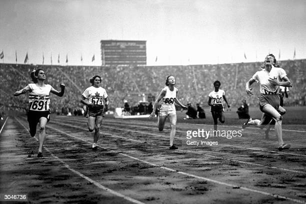 Fanny BlankersKoen far right of the Netherlands finishes first in the Women's 100m during the XIV Olympic Games Circa August of 1948 in London England