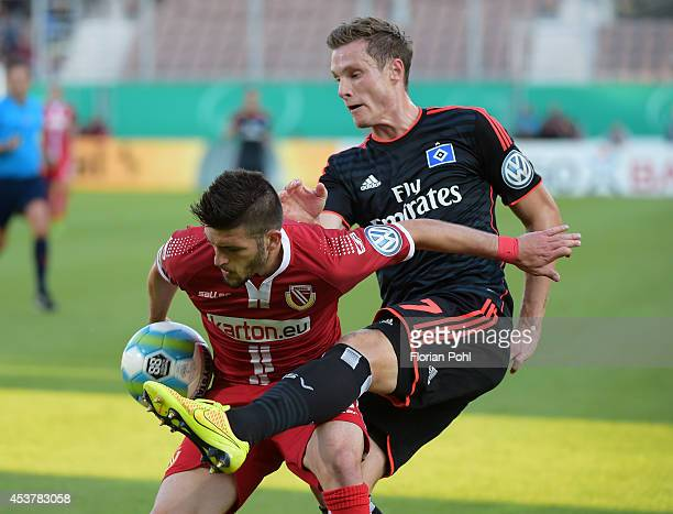 Fanol Perdedaj of FC Energie Cottbus competes with Marcell Jansen of Hamburger SV during the DFP Cup first round match between Energie Cottbus and...