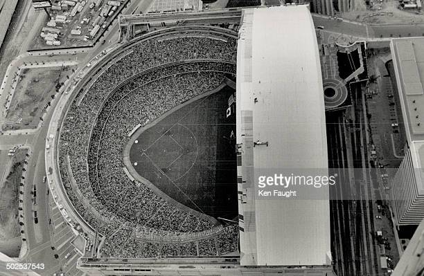 Fans and ballplayers are little more than dots in this bird'seye view of the jampacked SkyDome taken last night from a window washer's cage on the CN...