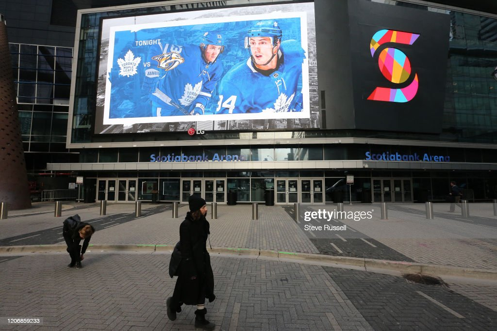 fans and  commuters walk past Scotiabank Arena where the Toronto Maple Leafs and the Nashville Predators were supposed to play tonight. The NHL along with the NBA, MLB, NLS and MLS have suspended all games in order to slow the spread of COVID-19 : News Photo