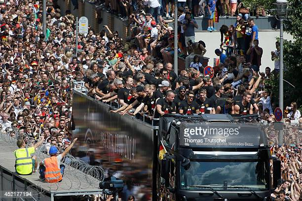 Fans and construction workers waving the German national soccer team near Reichstag building on July 15 2014 in Berlin Germany Thousands of football...