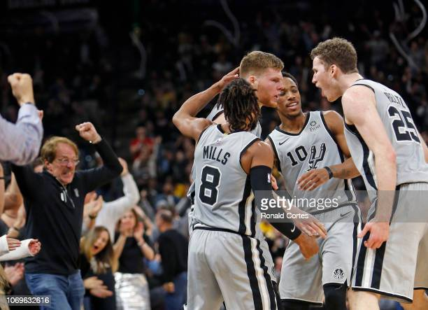 Fans and Davis Bertans of the San Antonio Spurs reacts as he do teammates Patty Mills and DeMar DeRozan and Jakob Poeltl after a three against the...