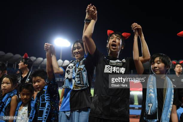 Fans and Kengo Nakamura of Kawasaki Frontale celebrate their side's 10 victory after the JLeague J1 match between Kawasaki Frontale and Vegalta...