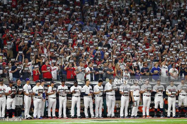 Fans and players hold Stand Up to Cancer signs during the 2019 MLB All-Star Game, presented by Mastercard at Progressive Field on July 09, 2019 in...