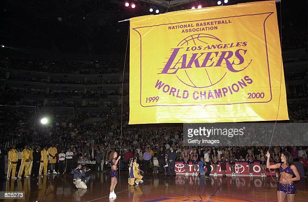 Fans and players watch as a giant banner is lowered after a ceremony honoring the Los Angeles Lakers as the current NBA champions November 1 2000 in...
