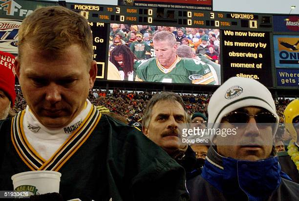 Fans and quarterback Brett Favre bow their heads in support for former Packer Reggie White during a moment of silence before the Minnesota Vikings...