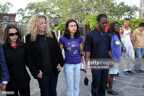 Fans and staff of US pop star Michael Jackson hold hands, 01 June 2005, as they pray in front of the entrance to their idol's Neverland ranch in Los...
