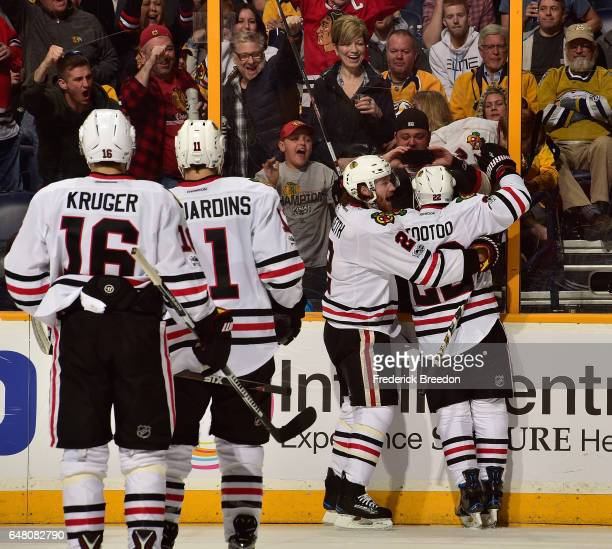 Fans and teammates join Jordin Tootoo of the Chicago Blackhawks after his scoring of a goal against his former team the Nashville Predators during...