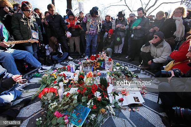 Fans and well wishers gather at the Strawberry Fields Memorial to sing songs and leave flowers as they commemorate the 30th anniversary of the death...