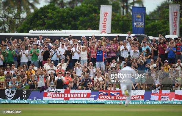 Fans applaud as the ball makes it's way to the boundary from the bat of Rory Burns during Day One of the First Test match between Sri Lanka and...