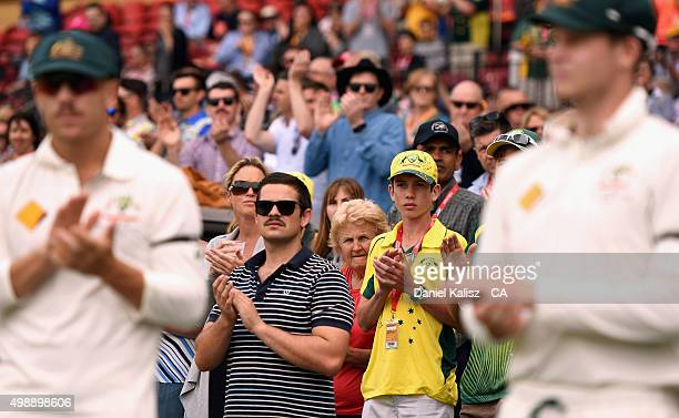 Fans applaud during a minute's silence for the late Phillip Hughes during day one of the Third Test match between Australia and New Zealand at...