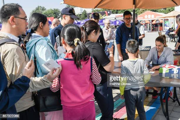 Fans are queuing to get an autograph from Alize Cornet of France at the merchandise booth on day five of the 2017 China Open at the China National...