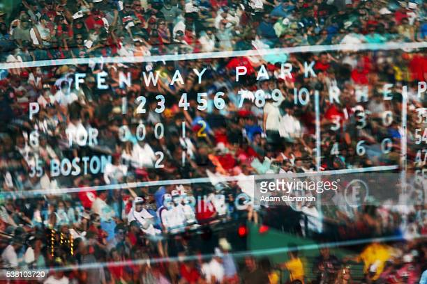 Fans are reflected in front of the Green Monster scoreboard during the Boston Red Sox vs the Tornoto Blue Jays game at Fenway Park on June 4 2016 in...