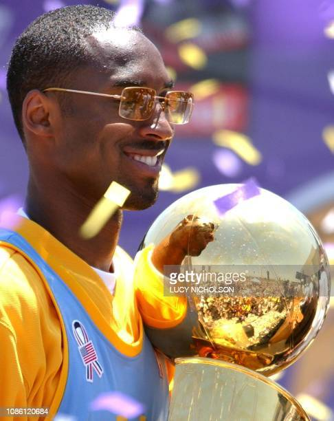 Fans are reflected in the NBA championship trophy as Los Angeles Lakers' guard Kobe Bryant celebrates the team's third consecutive NBA championship...
