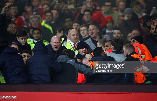 Fans are restrained by stewards after the UEFA Europa League round of 16 second leg match between Manchester United and Liverpool at Old Trafford on...