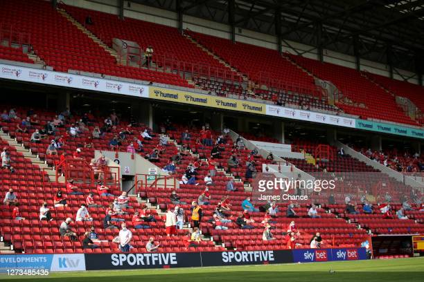 Fans are seen sitting in the stands socially distanced and wearing face masks during the Sky Bet League One match between Charlton Athletic and...