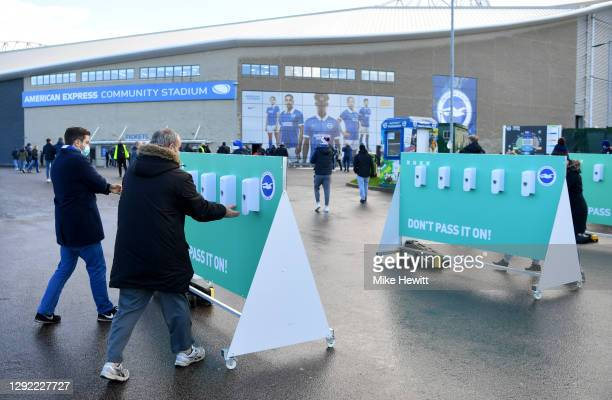 Fans are seen using a hand sanitizer station outside the stadium prior to the Premier League match between Brighton & Hove Albion and Sheffield...