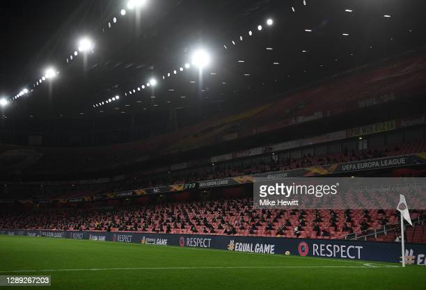 Fans are seen watching the game while abiding to social distancing rules during the UEFA Europa League Group B stage match between Arsenal FC and...