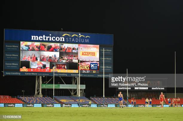 Fans are seen watching the match at home on the big screen during the round 2 AFL match between the Gold Coast Suns and the West Coast Eagles at...