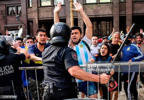 Fans argue with riot police as they try to reach the Casa Rosada presidential palace to pay tribute to late Argentine football legend Diego Maradona...