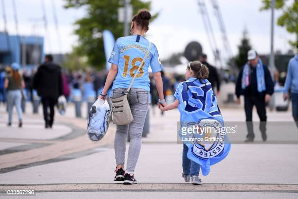 Fans arrive ahead of the Premier League match between Manchester City and Fulham FC at Etihad Stadium on September 15 2018 in Manchester United...