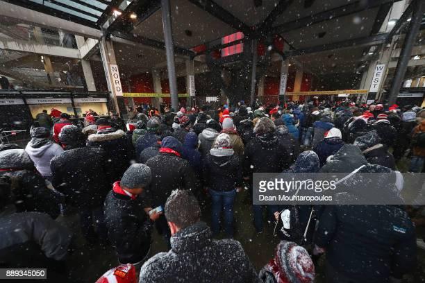Fans arrive as the heavy snow falls prior to the Bundesliga match between 1 FC Koeln and SportClub Freiburg at RheinEnergieStadion on December 10...