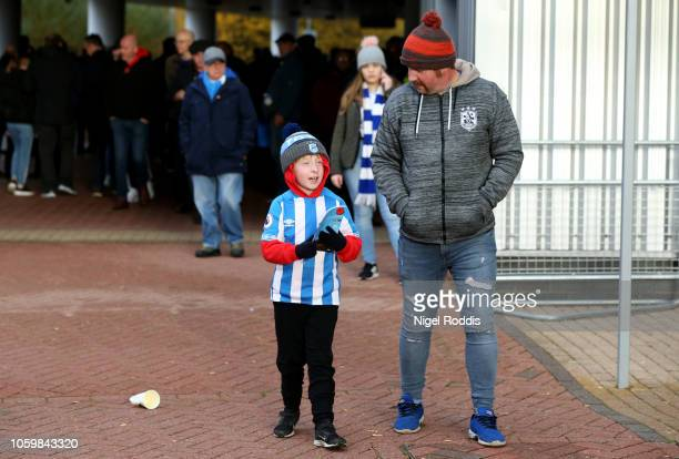 Fans arrive at the stadium prior to the Premier League match between Huddersfield Town and West Ham United at the John Smith's Stadium on November 10...