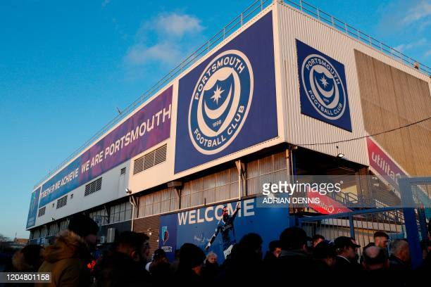 Fans arrive for the English FA Cup fifth round football match between Portsmouth and Arsenal at Fratton Park stadium in Portsmouth, southern England,...