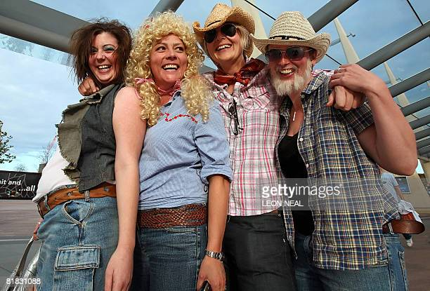 Fans arrive in costume as US country music singer Dolly Parton prepares to perform onstage in London as part of her Backwoods Barbie world tour on...