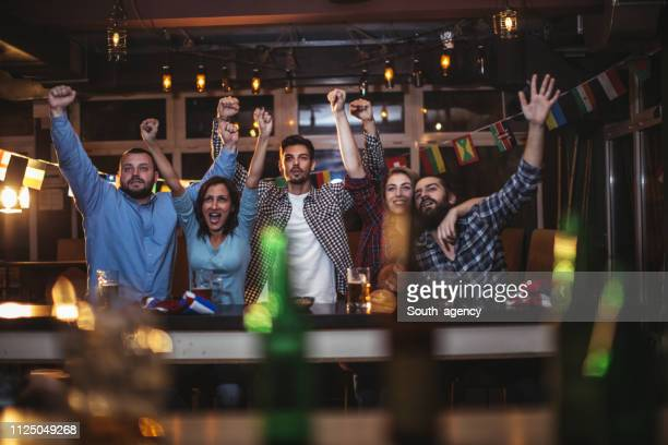 fans at the bar celebrating together - international soccer event stock pictures, royalty-free photos & images