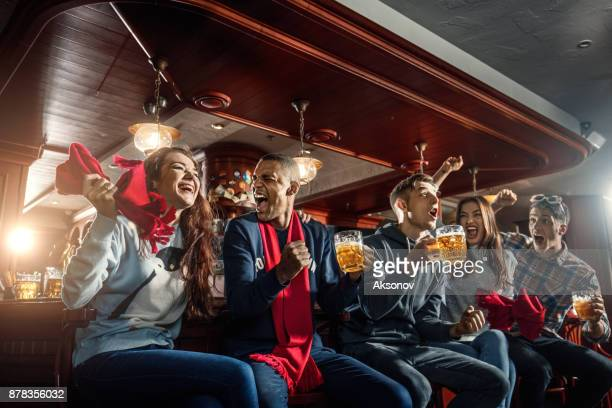 fans at the bar joyfully screaming and celebrate victory of their favorite sports team - american football sport stock photos and pictures