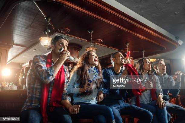 Fans at the bar joyfully screaming and celebrate victory of their favorite sports team