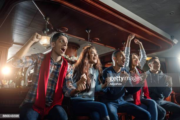 fans at the bar joyfully screaming and celebrate victory of their favorite sports team - american football sport stock pictures, royalty-free photos & images