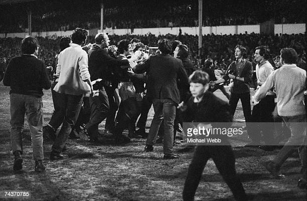 Fans at White Hart Lane surrounding Frank McLintock and Eddie Kelly after Arsenal scored in the last minute of the match against Tottenham Hotspur to...