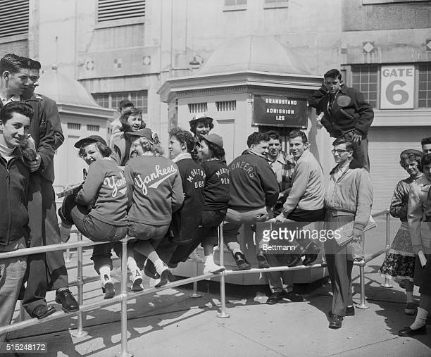 Fans at Yankee Stadium happily perch on railings while waiting for the ticket booth to open for the Yankees' opening day game against the Boston Red...