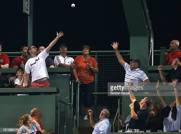 Fans atop the Green Monster try for a home run ball by Toronto Blue Jays designated hitter Edwin Encarnacion in the third inning as the Boston Red...