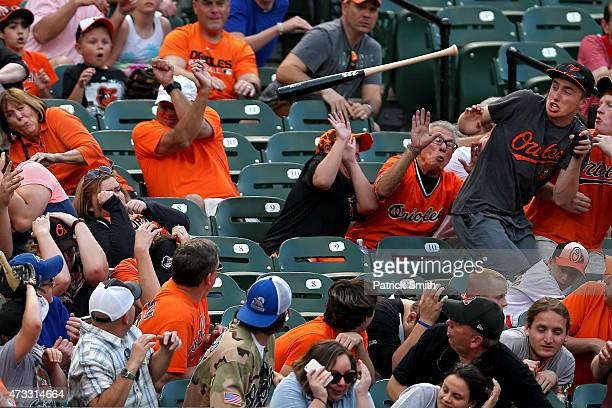 Fans attempt to dodge the loose bat of Josh Donaldson of the Toronto Blue Jays in the third inning against the Baltimore Orioles at Oriole Park at...